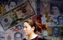 """El ministro de Finanzas de Japón, Taro Aso, dijo el martes que Tokio respondería rápidamente a las variaciones del tipo de cambio en línea con los acuerdos del G-7 y el G-20, aunque el país no intervendría tan """"fácilmente"""" en los mercados de divisas. En la imagen de archivo, una mujer camina junto a una tienda de cambio en Kuala Lumpur, Malaysia.  REUTERS/Olivia Harris"""