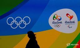 Журналист проходит мимо логотипа Игр в Рио 14 июня 2016 года. Российские тяжелоатлеты могут не попасть на Олимпиаду в Рио-де-Жанейро из-за неудовлетворительных допинг-проб, уже стоивших участия в Играх представителям российской сборной по легкой атлетике. REUTERS/Sergio Moraes