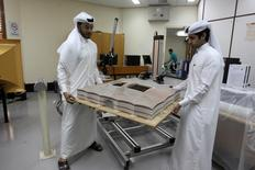 Mechanical engineers Abdullah Mojeb Aldar (L), 26, and Fahad al-Musalam, 24, move a 3d-printed model of QatarÕs Al Bayt stadium, which will host a World Cup semi-final in 2022, at a laboratory at Qatar University in Doha, Qatar June 16, 2016. REUTERS/Ibraheem Al Omari