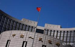 Флаг Китая над зданием центробанка страны в Пекине 3 апреля 2014 года. Народный банк Китая сообщил в понедельник, что продолжит проводить осторожную монетарную политику и предупредительную бюджетную политику. REUTERS/Petar Kujundzic/File Photo