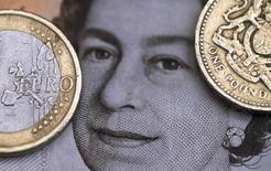 Ilustración fotográfica de una moneda de dos euros junto a una de una libra, sobre un retrato de la Reina Isabel. 16 de marzo de 2016. La libra esterlina  rebotaba cerca de medio centavo de dólar al comienzo de las operaciones del lunes en Londres, pero aún está un 2 por ciento por debajo de los niveles con los que cerró el viernes, su peor día en la historia moderna. REUTERS/Phil Noble/Illustration/File Photo