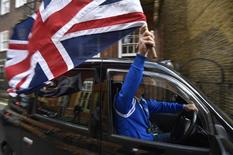 A taxi driver holds a Union flag, as he celebrates following the result of the EU referendum, in central London, Britain June 24, 2016.    REUTERS/Toby Melville