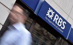 Un hombre camina cerca de una sucursal de Royal Bank of Scotland (RBS), en Londres, Gran Bretaña. 27 de agosto de 2014. El Gobierno de Reino Unido postergó la venta de sus participaciones en Royal Bank of Scotland  y Lloyds Banking Group este año tras la votación a favor de una salida británica de la Unión Europea, dijeron fuentes. REUTERS/Toby Melville/File Photo