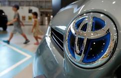 Visitors walk past a logo of Toyota Motor Corp on a Toyota Prius hybrid vehicle at the company's showroom in Tokyo August 5, 2014.   REUTERS/Yuya Shino/File Photo