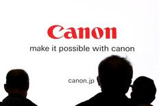People are silhouetted against a display of the Canon brand logo at the CP+ camera and photo trade fair in Yokohama, Japan, February 25, 2016. REUTERS/Thomas Peter/File Photo