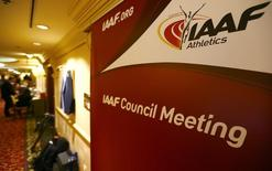 Journalists are seen near a logo of the International Association of Athletics Federations (IAAF) at a hotel where the IAAF council holds a meeting in Vienna, Austria, June 17, 2016.  REUTERS/Leonhard Foeger