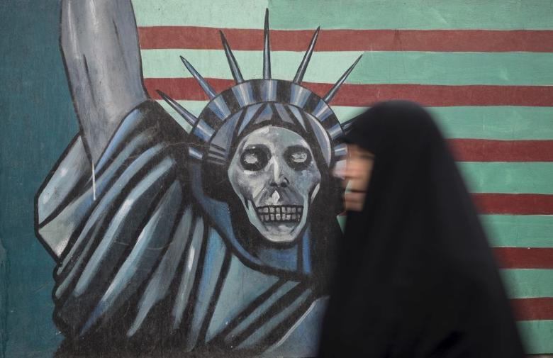 An Iranian woman walks past an anti-U.S. mural painted on the wall of the former U.S. Embassy in Tehran in a file photo.  REUTERS/Raheb Homavandi/TIMA