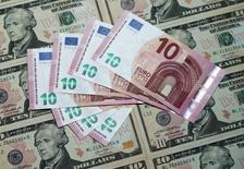 Billetes de 10 euros sobre unos billetes de 10 dólares en una ilustración fotográfica realizada en Viena, mar 16, 2015. El dólar se fortalecerá el próximo año pese a las menores probabilidades de que la Reserva Federal suba las tasas de interés, por preocupaciones de que la votación de Reino Unido para salir de la Unión Europea lleve a una desaceleración mayor del comercio y la inversión, mostró un sondeo de Reuters.      REUTERS/Heinz-Peter Bader