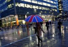 Workers walk in the rain at the Canary Wharf business district in London, Britain November 11, 2013. REUTERS/Eddie Keogh/File Photo