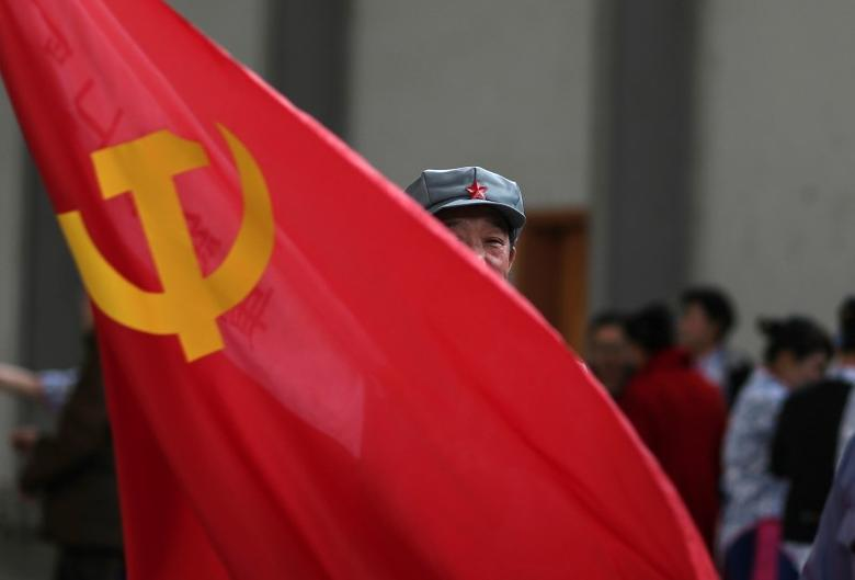 A participant waves a Chinese Communist Party flag as he waits backstage before his performance at a line dancing competition in Kunming, Yunnan province January 31, 2015. REUTERS/Stringer
