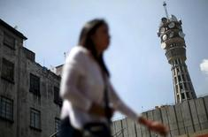 Una mujer pasa frente a una torre de telecomuniaciones en Ciudad de México, oct 8, 2015. El regulador de las telecomunicaciones en México anunció el miércoles que abrió una investigación para determinar la probable existencia de operadores con poder sustancial en los mercados de redes de telecomunicaciones que ofrecen servicios de voz, datos y/o video.  REUTERS/Edgard Garrido