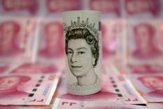 Un billete de 10 libras esterlinas sobre varios billetes de 100 yuanes chinos, en Pekín. 21 de enero de 2016. El rol de Londres como centro clave de operaciones con yuanes probablemente no se verá afectado por la decisión de Reino Unido de dejar la Unión Europea, y el nuevo escenario incluso podría alentar la internacionalización de la divisa china al favorecer este tipo de transacciones en otras ciudades dentro del bloque. REUTERS/Jason Lee/Illustration/File Photo