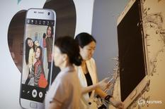 Женщины проходтят мимо рекламы телефонов Samsung Electronics в Сеуле 4 июля 2016 года. Технологический гигант Samsung Electronics Co Ltd сообщил в четверг о вероятном росте операционной прибыли во втором квартале на 17,4 процента в годовом выражении, что стало  рекордным показателем более чем за два года благодаря продажам смартфона Galaxy S7. REUTERS/Kim Hong-Ji