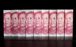 Fotografía ilustrativa de billetes de 100 yuanes chinos, tomada el 11 de julio de 2013. Las reservas de divisas de China subieron inesperadamente en junio en 20.000 millones de dólares a 3,21 billones de dólares, mostraron el jueves datos del banco central, rebotando desde el mínimo en cinco años que anotaron en mayo. REUTERS/Jason Lee/File Picture Illustration