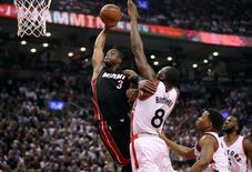May 11, 2016; Toronto, Ontario, CAN; Miami Heat guard Dwyane Wade (3) goes to the basket but is denied by Toronto Raptors center Bismack Biyombo (8) in game five of the second round of the NBA Playoffs at Air Canada Centre. Mandatory Credit: Tom Szczerbowski-USA TODAY Sports