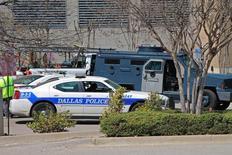 Полиция и спасатели у здания в ходе противостояния с вооруженным человеком в Далласе, штат Техас, 25 марта 2014 года. Неизвестные снайперы открыли огонь с крыш в Далласе во время протестов против полицейского насилия в отношении чернокожих, убив пятерых сотрудников полиции, которая назвала атаку тщательно спланированной и задержала ряд подозреваемых. REUTERS/Jana J. Pruet