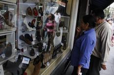 Una pareja mira los precios de los zapatos en una tienda en Ciudad de México. 26 de octubre de 2013. El índice de confianza del consumidor de México subió un 0.5 por ciento en junio contra el mes precedente en medio de un mayor optimismo de las familias por el futuro económico del país, mostraron el viernes cifras oficiales ajustadas por estacionalidad. REUTERS/Tomas Bravo
