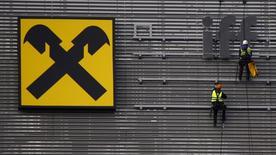 El banco Santander va a analizar la compra de la división polaca del austriaco Raiffeisen, lo que eleva a cinco el número de potenciales interesados, dijeron a Reuters dos fuentes del sector. En la imagen, unos trabajadores colocan las letras del logo de Raiffeisen Polbank en su nueva oficina en Varsovia, el 29 de octubre de 2015. REUTERS/Kacper Pempel