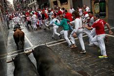 Runners sprint along Nunez del Cuvillo bulls during the seventh running of the bulls at the San Fermin festival in Pamplona, northern Spain, July 13, 2016. REUTERS/Susana Vera
