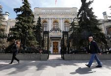 Люди проходят мимо здания Банка России в Москве 29 апреля 2016 года. Банк России оценил годовые темпы трендовой инфляции в июне 2016 года в 9,0 процента по сравнению с 9,3 процента в предыдущем месяце. REUTERS/Maxim Zmeyev