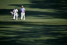 Lee Westwood of Britain walks down the second fairway with his caddie Billy Foster during first round play of the Masters golf tournament at the Augusta National Golf Course in Augusta, Georgia April 9, 2015.  REUTERS/Jim Young