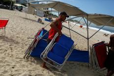Un hombre carga sillas para arrendar a visitantes en la playa de Ipanema en Río de Janeiro, 29 de abril de 2014. La actividad en el sector de servicios de Brasil se contrajo más de lo esperado en mayo frente a un año atrás, mostraron el miércoles datos del Gobierno, lo que suma indicios de una difícil recuperación económica en el país sudamericano mientras las familias recortan gastos para paliar la crisis. REUTERS/Pilar Olivares/File Photo