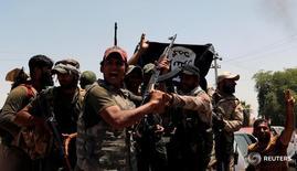 """Бойцы-шииты с сорванным флагом ИГ в Гарме, Ирак 26 мая 2016 года. Абу Умар аш-Шишани, выходец из Грузии, которого Пентагон называл """"министром войны"""" """"Исламского государства"""", был убит в бою в иракском городе аш-Ширкате, расположенном к югу от Мосула, сообщило поддерживающее ИГ новостное агентство в среду. REUTERS/Thaier Al-Sudani"""