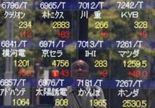 Un hombre aparece reflejado en una pantalla con cotizaciones afuera de una corredora en Tokio, Japón, el 11 de julio de 2016. Las bolsas de Asia operaban el jueves cerca de unos máximos de ocho meses por las expectativas de que el Banco de Inglaterra recortará las tasas de interés para evitar el riesgo de una recesión tras la decisión de Reino Unido de abandonar la Unión Europea. REUTERS/Issei Kato