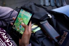 "A woman uses a portable battery pack to charge her phone while playing the augmented reality mobile game ""Pokemon Go"" by Nintendo in New York City, U.S. July 11, 2016.  REUTERS/Mark Kauzlarich"