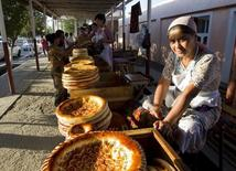 Женщина продает традиционные узбекские лепешки на придорожном рынке близ города Коканд. 30 августа 2012 года. Рост экономики Узбекистана замедлился в первой половине 2016 года до 7,8 процента с 8,1 процента за аналогичный период прошлого года, сообщила впятницу пресс-служба кабмина после заседания Кабинета министров по итогам работы за первое полугодие. REUTERS/Shamil Zhumatov