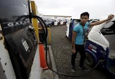 Un trabajador cargando su vehículo con gas licuado en una gasolinera en Lima, mayo 28, 2015. La actividad económica de Perú creció un 4,88 por ciento interanual en mayo, levemente más de lo previsto por analistas, impulsada por un nuevo repunte de la vital producción minera y de hidrocarburos, dijo el viernes el Gobierno.   REUTERS/Mariana Bazo