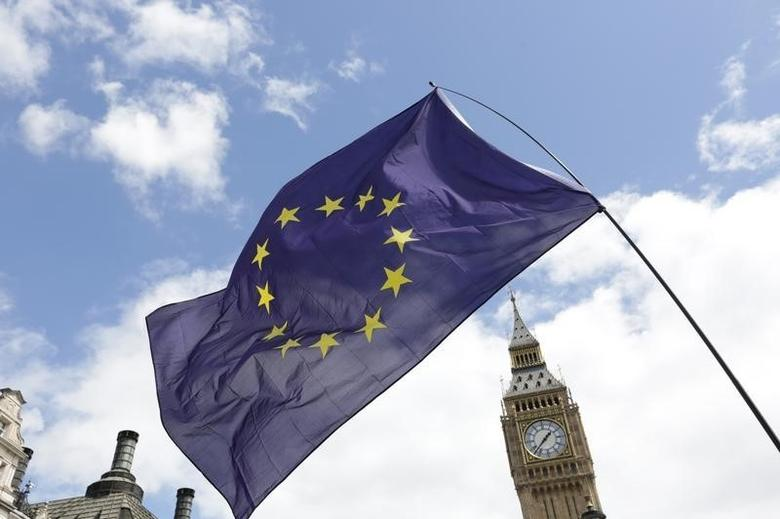 A European Union flag is held in front of the Big Ben clock tower in Parliament Square during a 'March for Europe' demonstration against Britain's decision to leave the European Union, central London, Britain July 2, 2016. REUTERS/Paul Hackett