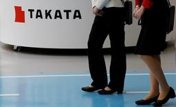 Women walk past a logo of Takata Corp on its display at a showroom for vehicles in Tokyo, Japan, May 11, 2016.   REUTERS/Toru Hanai/File Photo