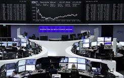 Traders work at their desks in front of the German share price index, DAX board, at the stock exchange in Frankfurt, Germany, July 19, 2016.     REUTERS/Staff/Remote