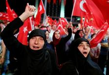 Сторонники президента Турции Тайипа Эрдогана размахивают флагами на демонстрации в его поддержку в Стамбуле 19 июля 2016 года. Турецкий Совет по высшему образованию запретил всем преподавателям вузов выезжать за границу, сообщил в среду гостелеканал TRT. Продолжая чистки и охоту за критиками после провального путча военных, власти заблокировали доступ к WikiLeaks, опубликовавшему утечку переписки членов правящей партии президента Тайипа Эрдогана. REUTERS/Ammar Awad