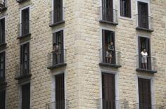 Люди на балконах дома в Барселоне 18 августа 2015 года. Жилищное строительство в Испании возвращается к жизни спустя восемь лет после ипотечного кризиса. Иностранные инвестиции дали толчок развитию строительной отрасли в Мадриде и Барселоне, а резкий скачок числа разрешений на строительство указывает на грядущий рост. REUTERS/Albert Gea