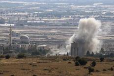 Дым клубится во время столкновений в сирийском селении Ахмадья. Вид с израильской стороны ограждения между Сирией и оккупированными Израилем Голанскими высотами. Сирийские повстанцы сообщили об израильском ударе вблизи Голанских высот. REUTERS/Baz Ratner