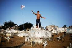 A man flies his kite in a cemetery in the Vila Operaria Favela of Rio de Janeiro, Brazil, June 25, 2016. REUTERS/Nacho Doce