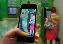 "A woman plays the augmented reality mobile game ""Pokemon Go"" by Nintendo, as a visitor uses an automated teller machine (ATM) at a branch of Sberbank in central Krasnoyarsk, Siberia, Russia, July 20, 2016. REUTERS/Ilya Naymushin"