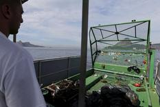 Funcionário coleta lixo na Baía de Guanabara no Rio de Janeiro. 1/7/2015.  REUTERS/Sergio Moraes