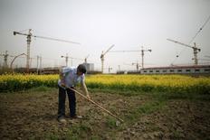 Shanghaï, chantier de construction d'immeubles d'appartements. La croissance économique en Chine devrait revenir à 6,5% cette année, soit le bas de la fourchette visée par Pékin, malgré une augmentation des dépenses publiques et un assouplissement de la politique monétaire censés empêcher un ralentissement plus marqué, montre une enquête de Reuters jeudi. /Photo prise le 21 mars 2016/REUTERS/Aly Song