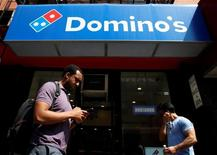 People pass by a Domino's Pizza restaurant in New York City, U.S., May 25, 2016.  REUTERS/Brendan McDermid