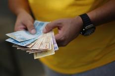 """Un hombre contando reales en Brasilia, jun 28, 2014. El Gobierno brasileño podría ofrecer al menos 1.000 millones de dólares en un nuevo bono global con vencimiento en febrero de 2047, con un rendimiento que estaría en el """"área muy inferior del 6 por ciento"""", dijo el jueves una fuente directamente involucrada en la operación.   REUTERS/Ueslei Marcelino"""