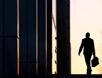 A worker arrives at his office in the Canary Wharf business district in London February 26, 2014.REUTERS/Eddie Keogh
