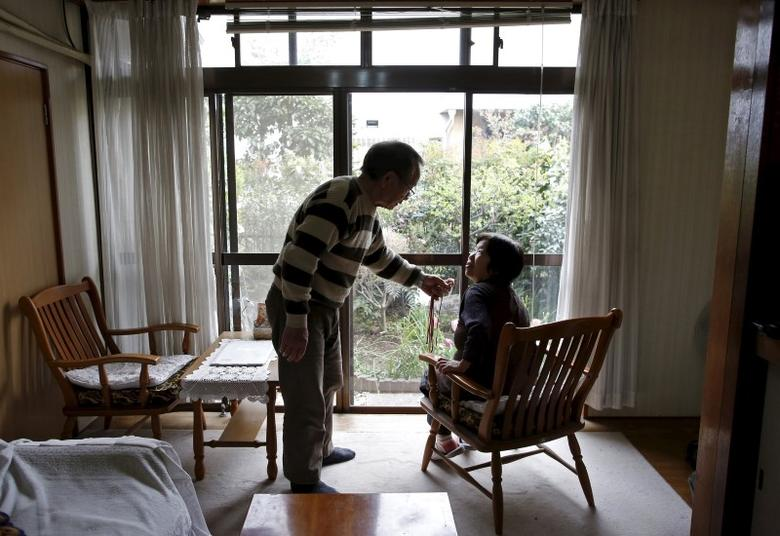 72-year-old Kanemasa Ito (L) and his 68-year-old wife Kimiko who was diagnosed with dementia 11 years ago, chat at their home in Kawasaki, south of Tokyo, Japan, April 6, 2016. REUTERS/Issei Kato/Files