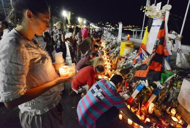 People form a human chain as they take candles and flowers left in tribute at makeshift memorials to the victims of the truck attack and place them along the Promenade des Anglais in Nice, France, July 18, 2016. REUTERS/Jean-Pierre Amet