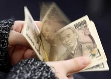 Женщина пересчитывает банкноты в 10000 иен. Иена достигла двухнедельного пика к евро и прибавила более 1 процента к доллару во вторник, в то время как трейдеры ослабили ожидания относительно масштаба новых мер стимулирования японских властей. REUTERS/Shohei Miyano/Illustration/File Photo