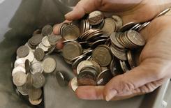 Кассир пересчитывает рублевые монеты. Рубль во вторник падает, переписывая одномесячные минимумы и к доллару, и к евро на фоне дешевеющей нефти и после прохождения накануне пика налогов; рынок также продолжал закладывать в котировки озабоченность руководства страны летним укреплением российской валюты, озвученную на прошлой неделе.  REUTERS/Ilya Naymushin