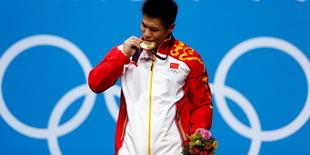 China's Xiaojun Lu bites his gold medal at the podium of the men's 77Kg weightlifting competition at the ExCel venue at the  London 2012 Olympic Games August 1, 2012. REUTERS/Grigory Dukor