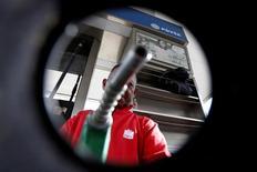 """Un trabajador apunta con un surtidor de combustible a una cámara en una gasolinera de PDVSA en Caracas, jul 21, 2016. El presidente de Petróleos de Venezuela (PDVSA), Eulogio Del Pino, dijo que anunciará """"próximamente"""" un canje de bonos de la firma estatal, según indicó el miércoles la publicación local especializada Petroguía.     REUTERS/Carlos Jasso"""